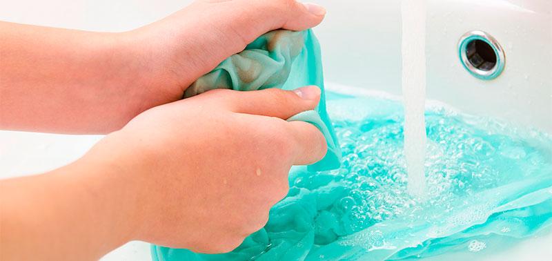 Mujer lavando manchas de maquillaje en ropa